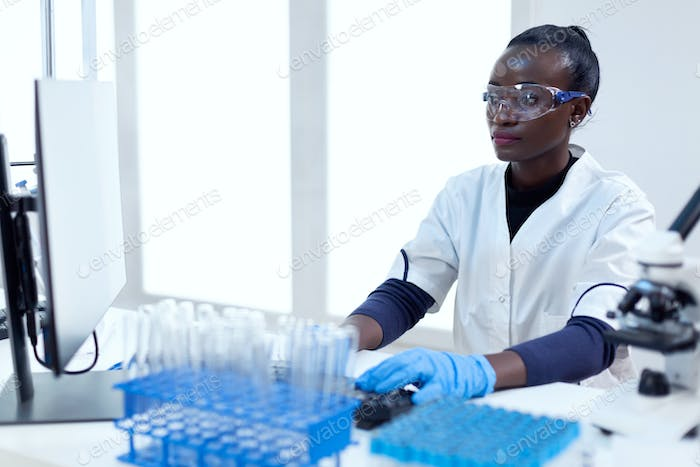 African biotechnology researcher works in bright modern laboratory