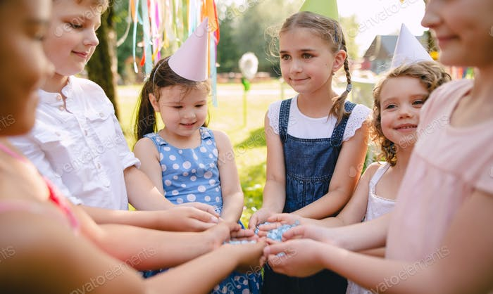 Children playing outdoors on birthday party in garden in summer.
