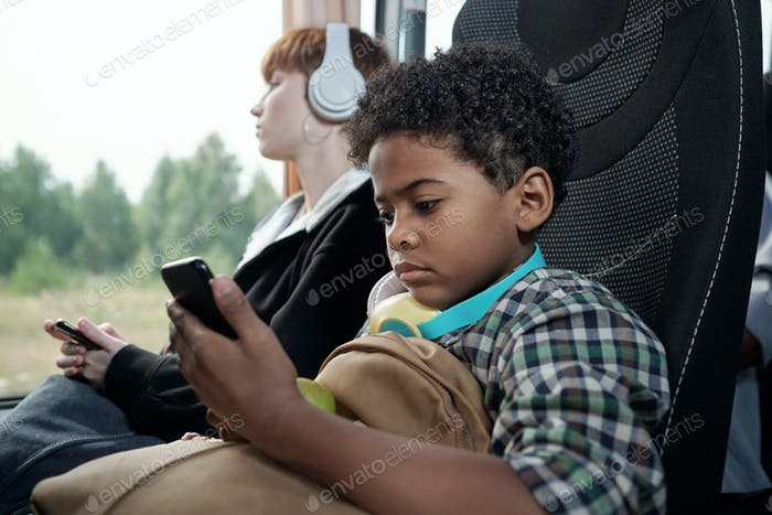 Little boy looking at screen of smartphone in the bus