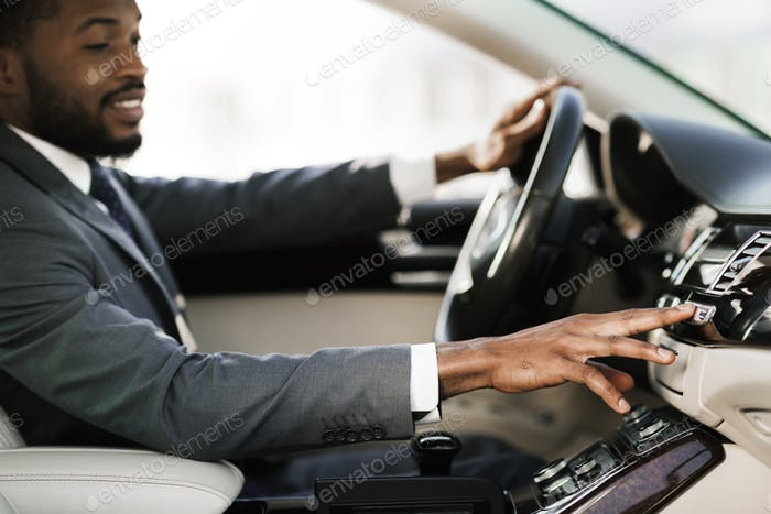 Relaxed Black Man Driving Car Listening Radio Sitting In Automobile