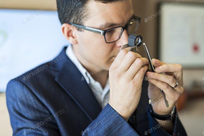 Juwelier untersucht Diamant durch Lupe