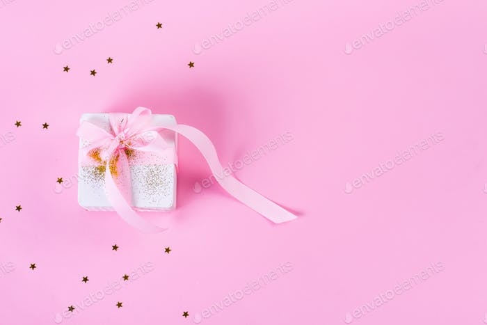 Gift or present box with confetti stars and pink ribbon on pastel pink background. Holiday pattern