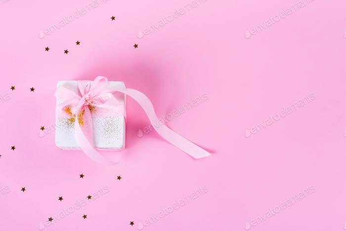 Geschenkbox oder Geschenkbox mit Konfetti Sternen und rosa Schleife auf pastellrosa Hintergrund. Urlaubsmuster