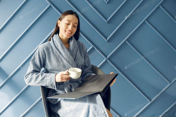 Beautiful girl standing in a studio in a blue bathrobe