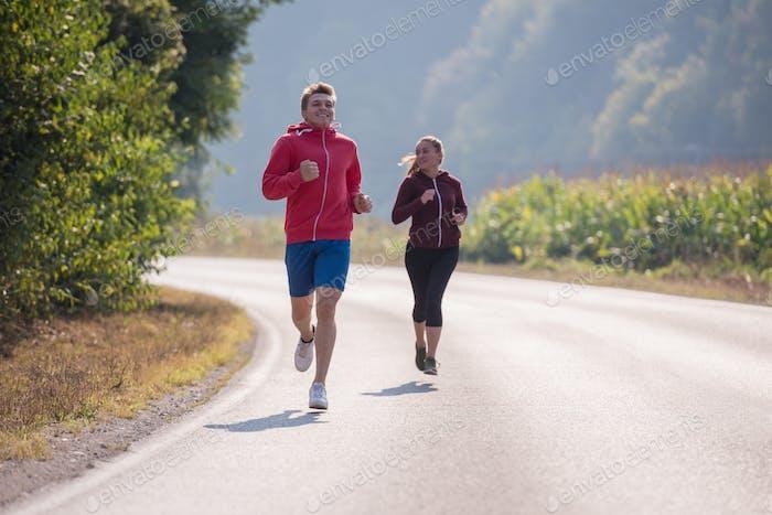jóvenes pareja trotar a lo largo de un país Carretera