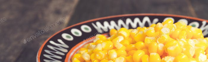 Banner of Canned corn in a brown bowl on wooden background.
