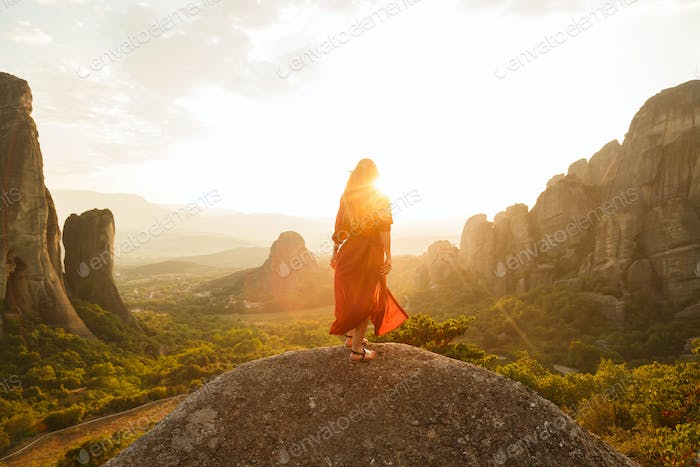 Girl in red flying dress looking at majestic sunset in Meteora valley, Greece