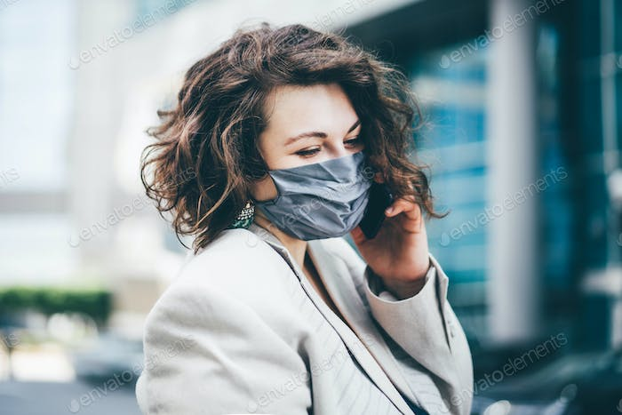 Businesswoman with mask talking on the phone in the city outdoors.