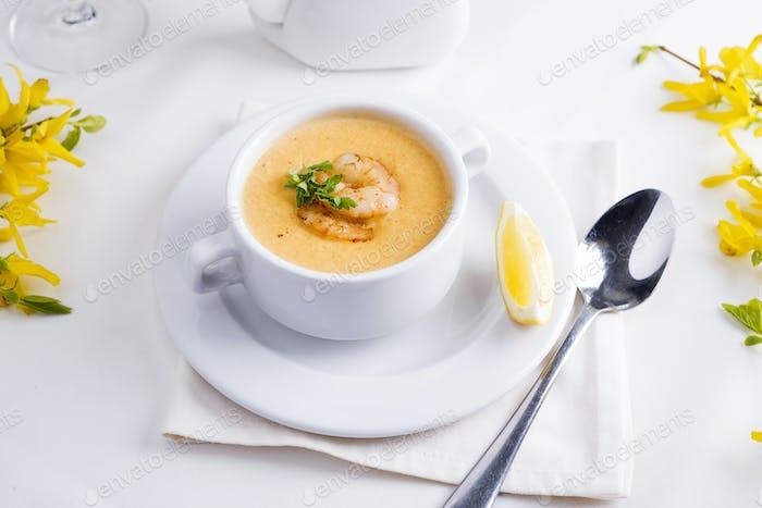 Cremige Tomatensuppe mit Meeresfrüchten und Zitrone auf weißem Hintergrund.
