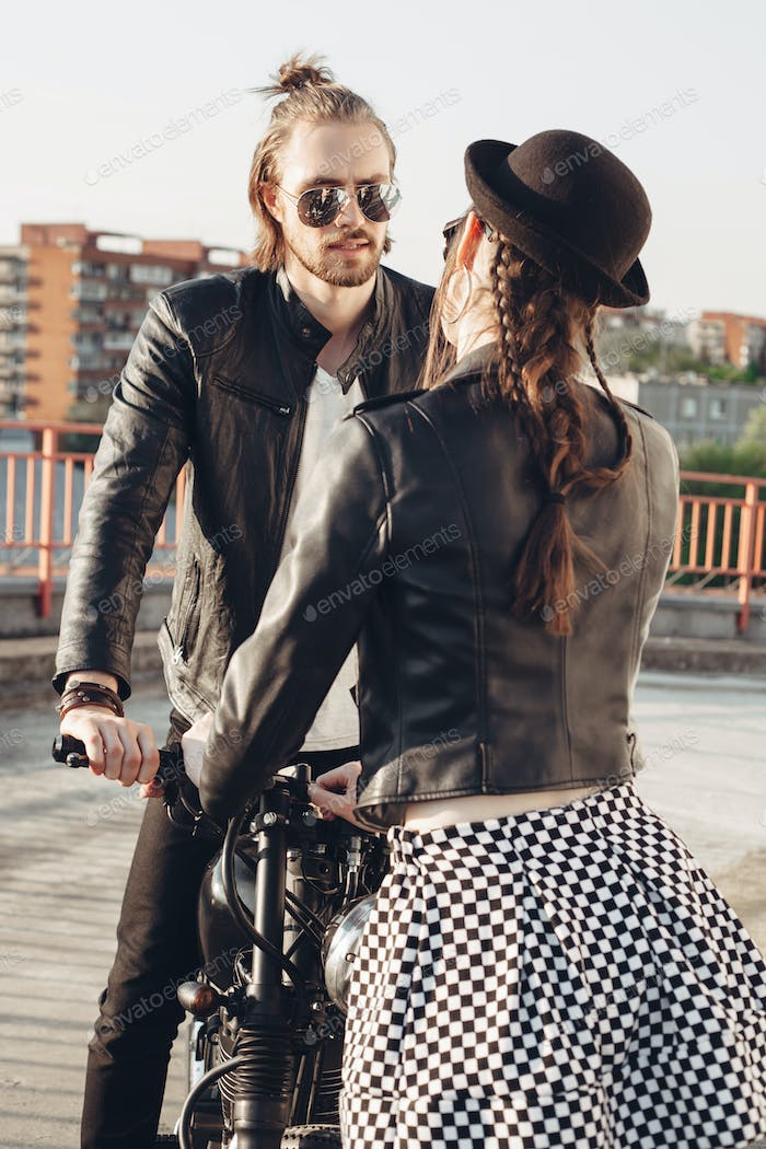 young couple sitting on vintage motorcycle