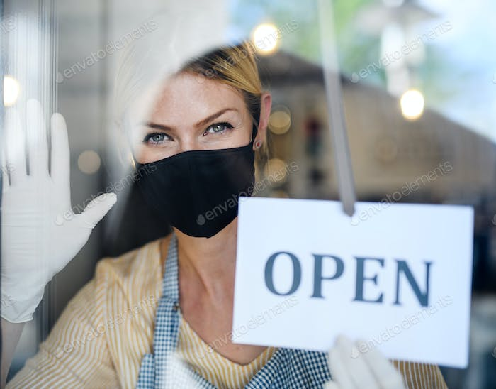 Coffee shop woman owner with face mask, open after lockdown quarantine