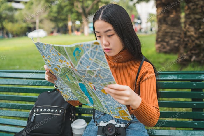 Asian woman looking at a map.