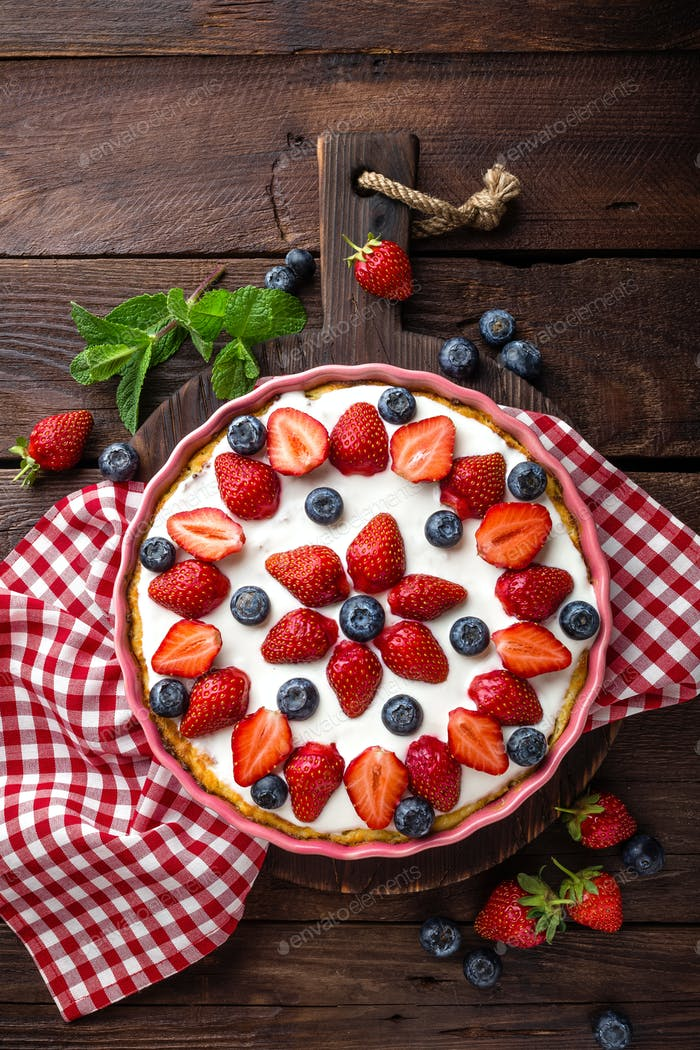 Delicious strawberry pie with fresh blueberry and whipped cream on wooden rustic table, cheesecake