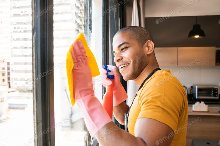 Male housekeeper cleaning glass window at home.