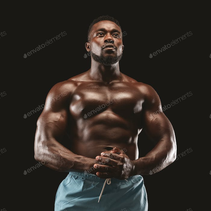 Portrait of handsome muscular sportsman demonstrating his body