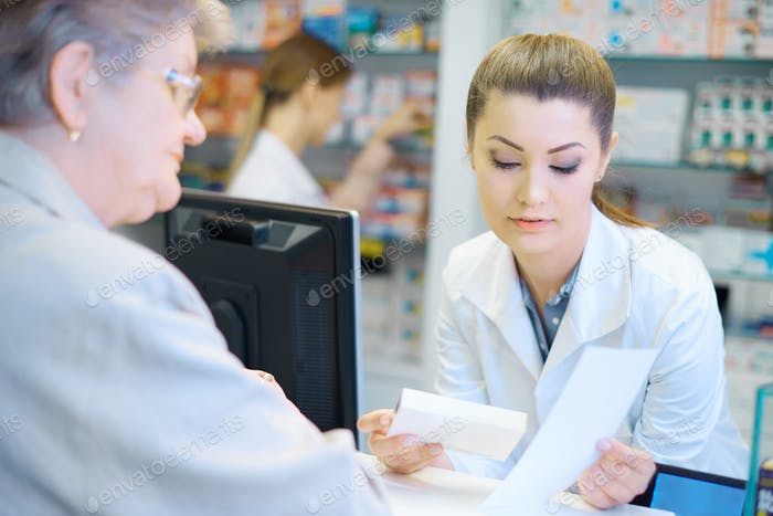 Mature woman discussing product with pharmacist
