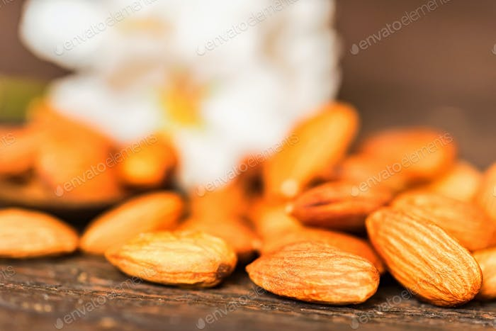 Almonds and white flowers on dark wooden surface