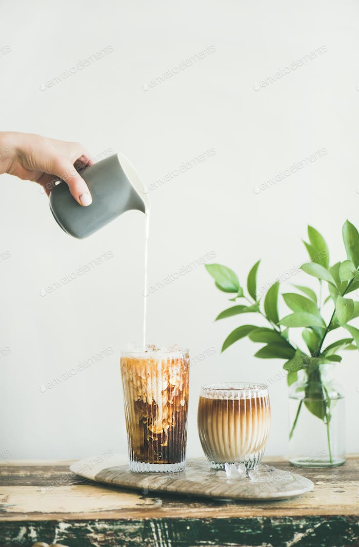 Iced coffee in a tall glass with cream poured over