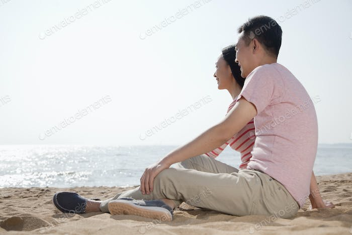 Couple sitting on the beach and looking out at the ocean