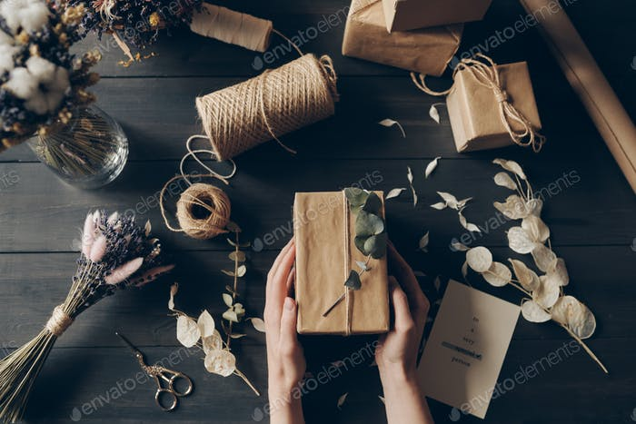 Directly above view of woman packing gifts into kraft paper