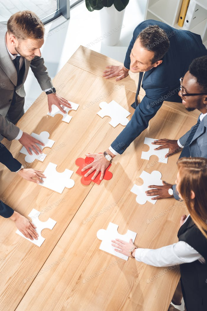 high angle view of businesspeople assembling puzzle on conference table