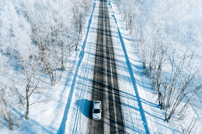 Aerial view of winter road with a car and snow covered trees.