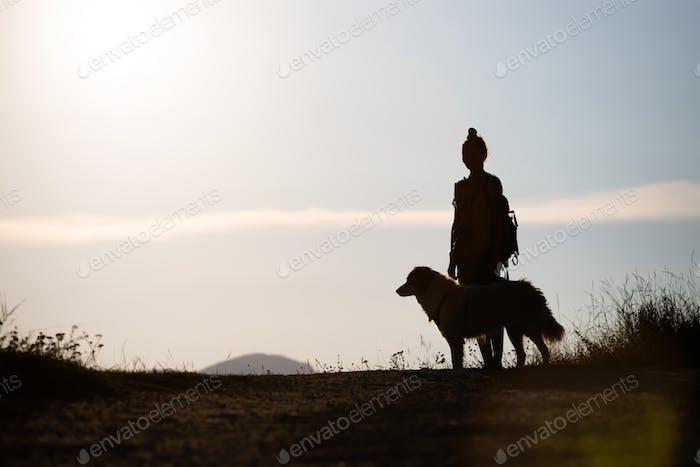 Frau mit ihrem Hund steht auf dem Hügel im Sonnenuntergang.