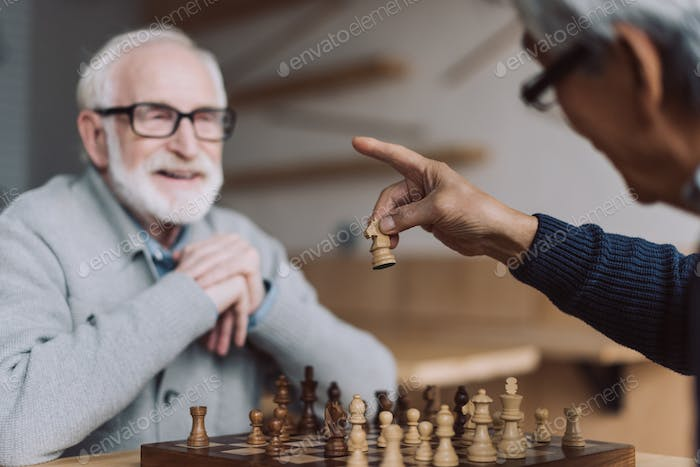 smiling senior men playing chess in bar