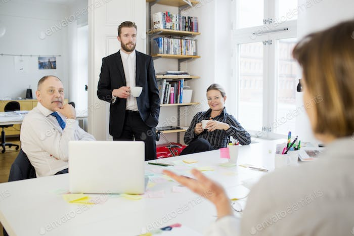 Business people listening to female colleague at desk in office