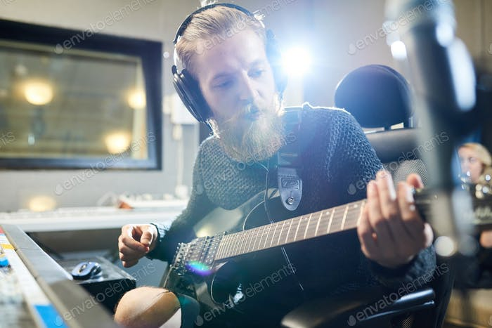 Bearded musician with guitar in sound studio