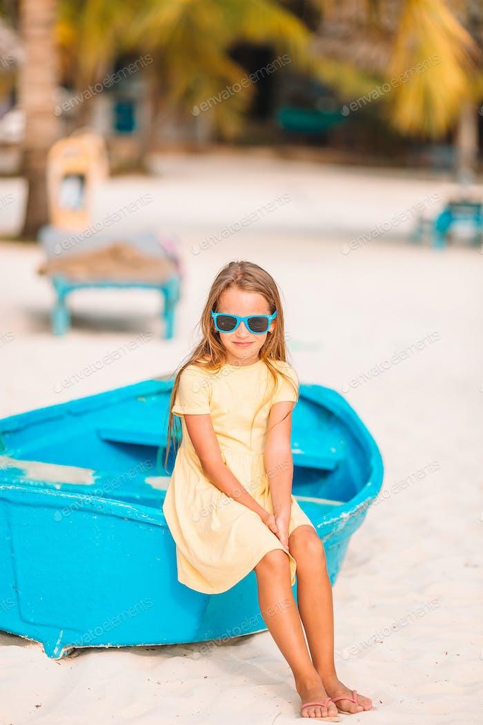 Adorable little girl on boat on white beach