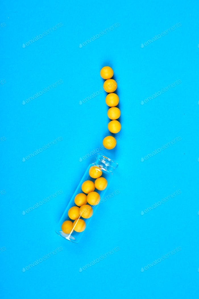Flat lay overhead of yellow pills in glass jar on blue background