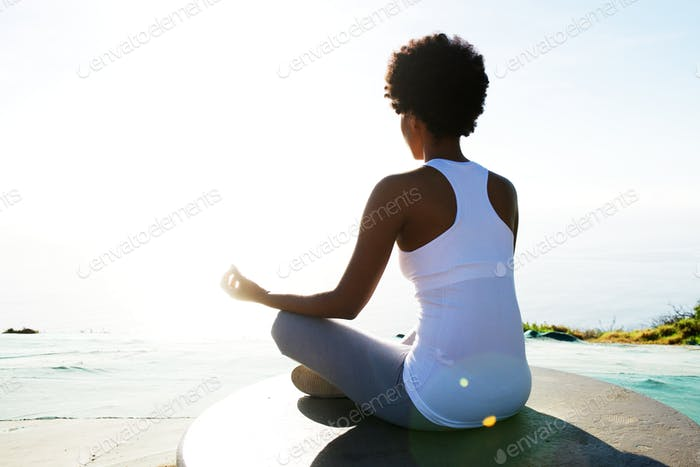 Young woman sitting at beach in yoga pose