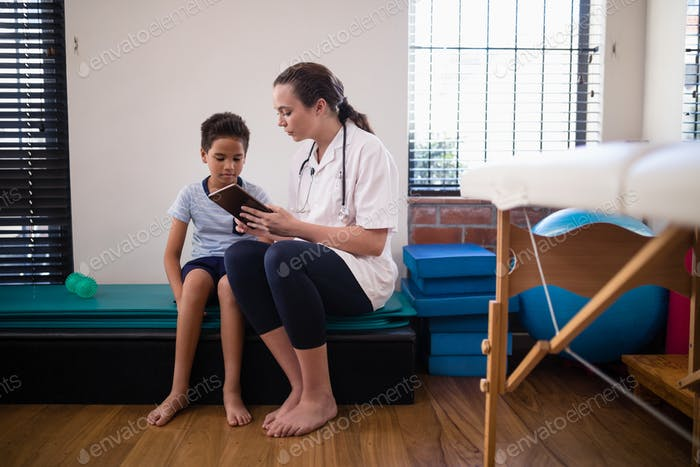 Female doctor showing digital tablet to boy against wall