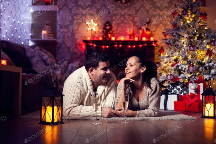Photo of young couple resting by the fireplaec in the christmas room