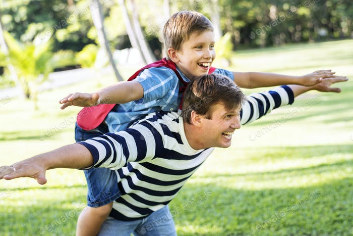 Superhero boy flying on the back of his dad