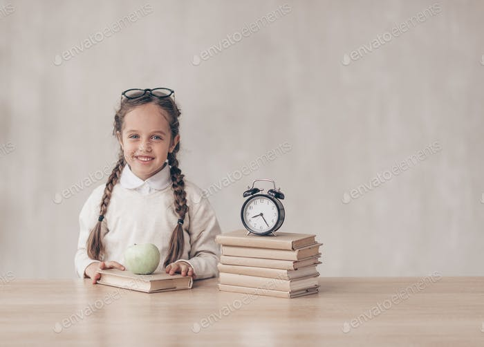 Smiling little girl at the desk