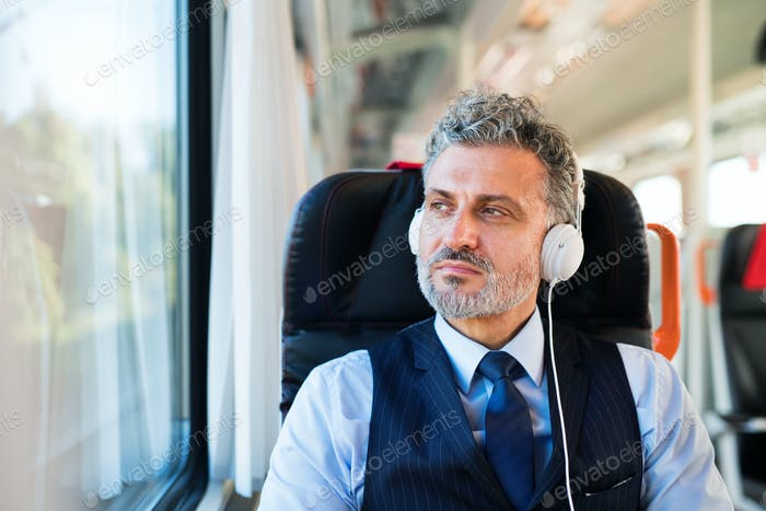 Mature businessman with headphones travelling by train.