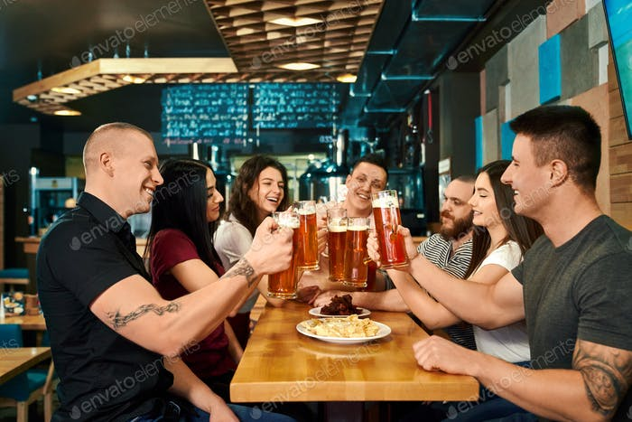 Company sitting at big table and enjoying ale in pub