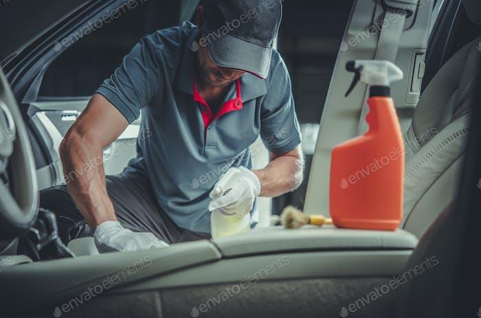 Caucasian Car Detailer Cleaning Modern Vehicle Interior