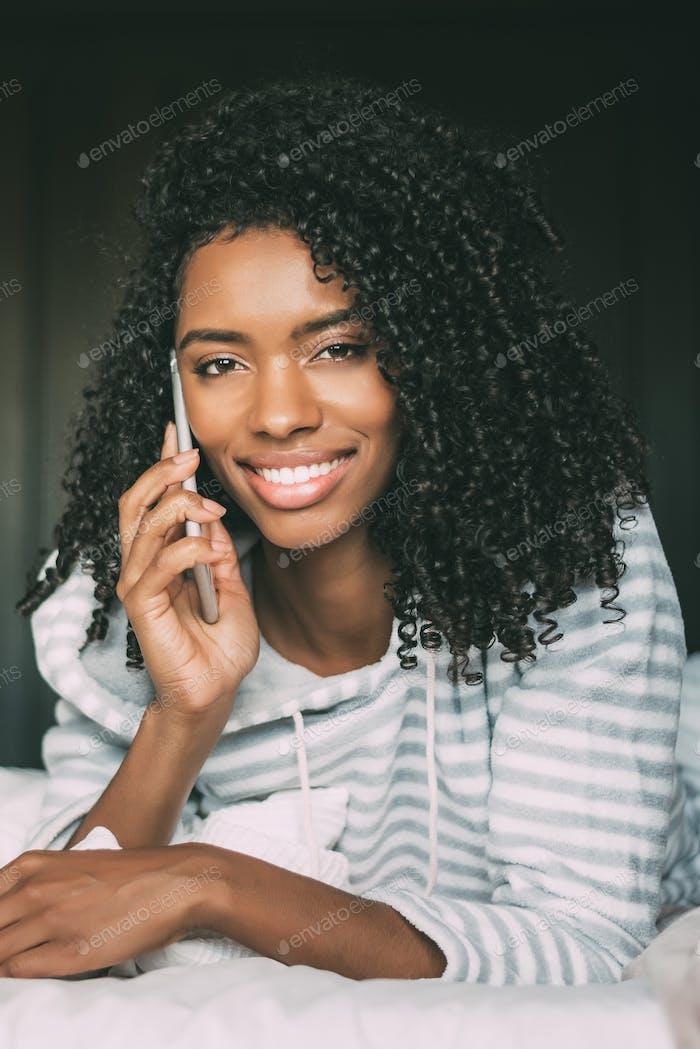 рядом с довольно черный женщина с вьющимися волосами со смартфоном на кровати глядя на камеру