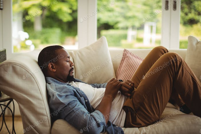 Man lying on sofa and using his smartwatch