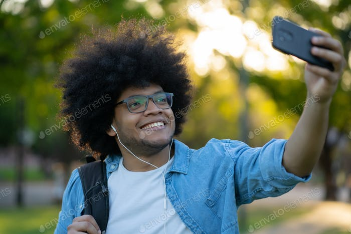 Latin man taking a selfie with phone outdoors.