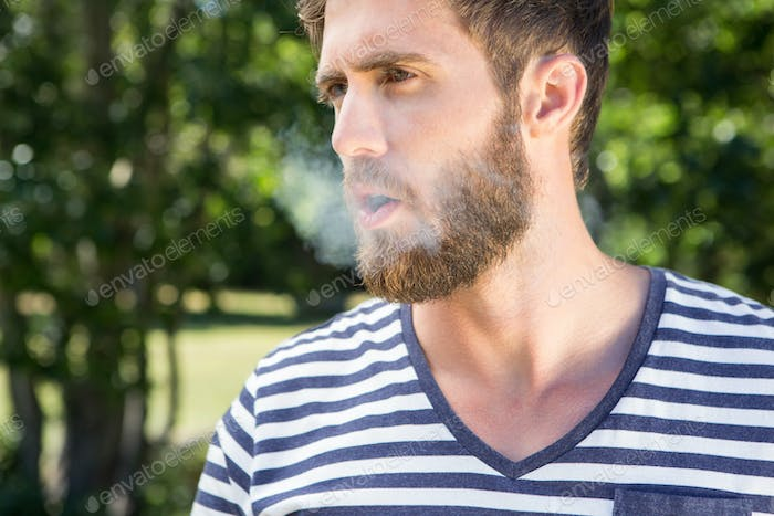 Hipster smoking electronic cigarette on a summers day