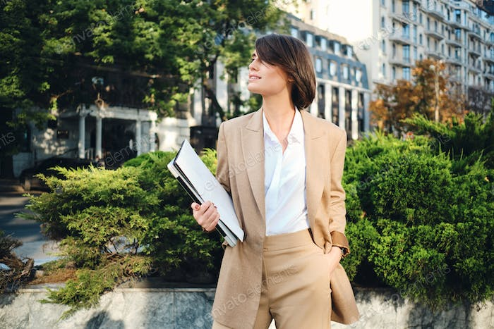 Young attractive smiling businesswoman in beige suit standing with laptop on city street