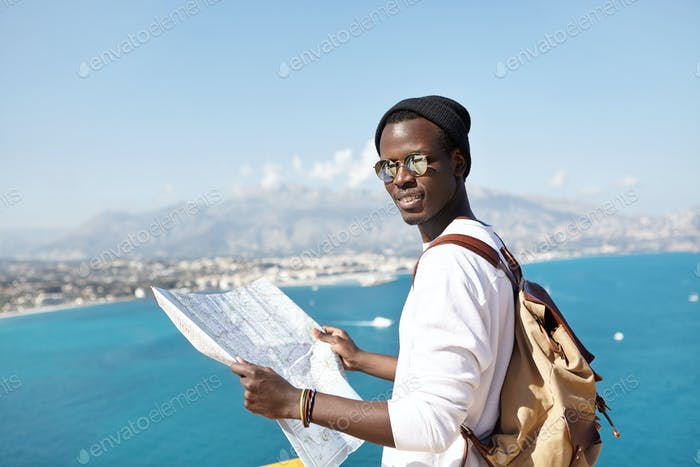 Retrato de joven viajero afroamericano mirando a la cámara con mapa de papel en las manos, usando s