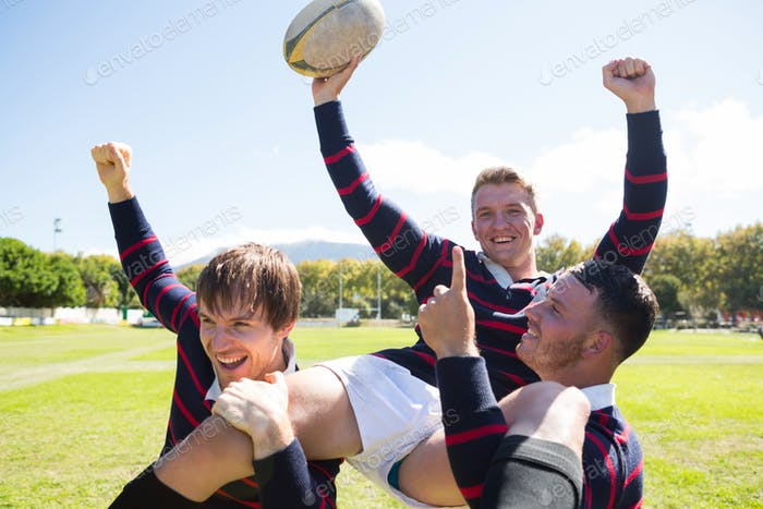 Portrait of happy rugby players enjoying at field
