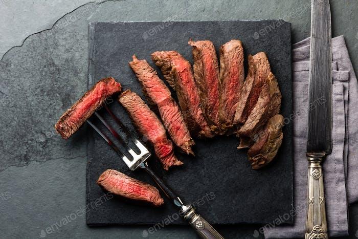 Medium rare beef steak on slate board, vintage cutlery, grey background