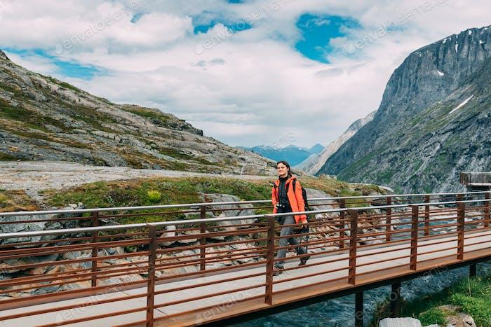 Trollstigen, Andalsnes, Noruega. Mujer joven caucásica viajero turista caminando plataforma de visualización cerca