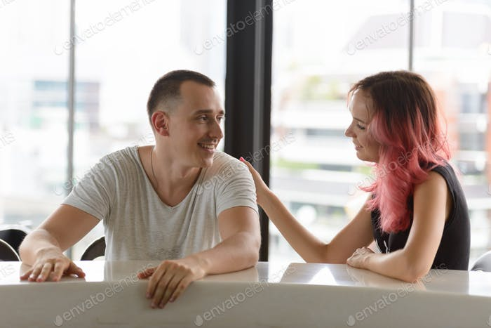 Portrait of happy couple talking together on the counter